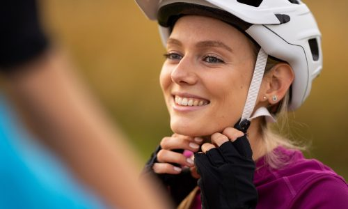happy young woman portrait face closing bike helmet smiling at her boyfriend, shallow focus