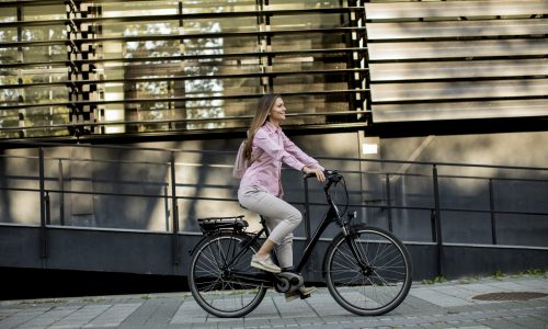 Young woman riding e bike in urban enviroment at sunny day
